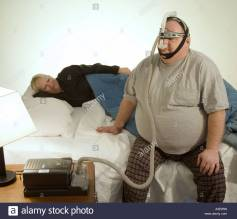 man-with-sleep-apnea-problems-readies-for-bed-as-his-wife-tries-to-A3E9RN