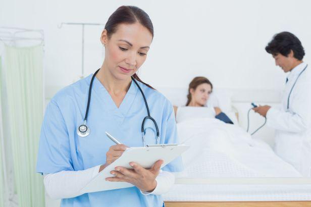nurse-in-blue-scrubs-charting-on-clipboard
