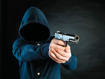 bigstock-Armed-Person-In-A-Hoodie-Is-Po-90195365